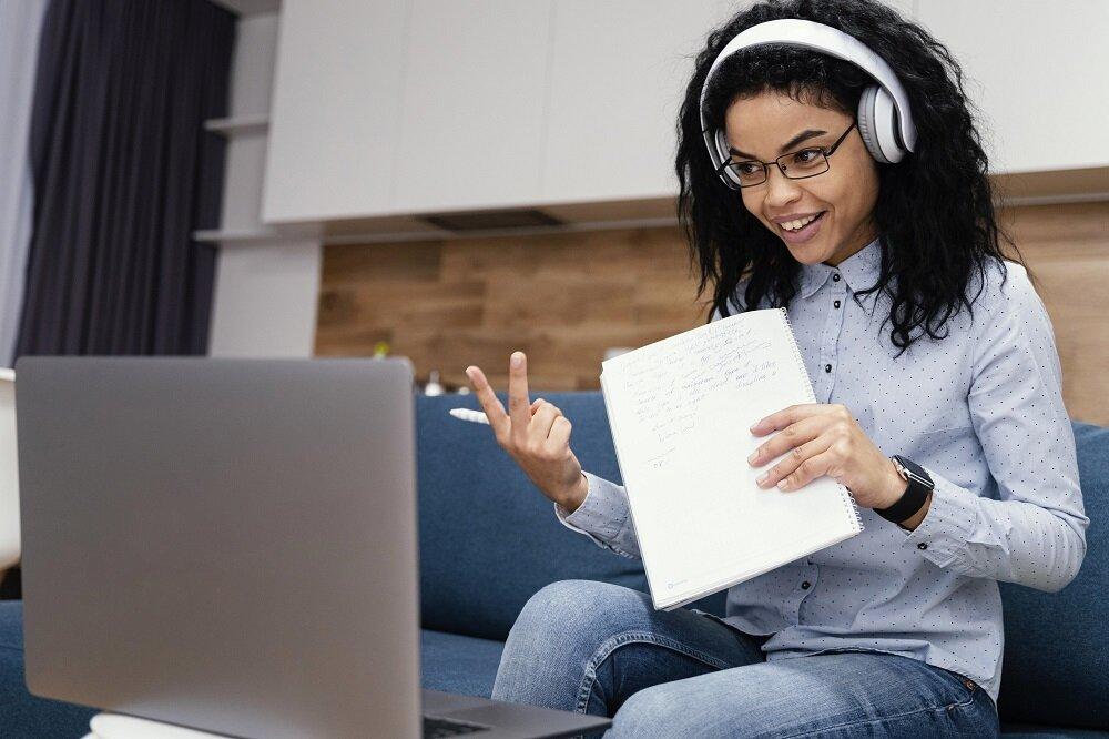 smiley-teenage-girl-with-headphones-during-online-school